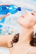 Woman drinking water, at fitness club