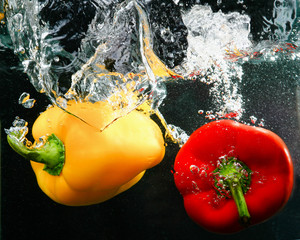 red and yellow peppers in water, isolated on black background