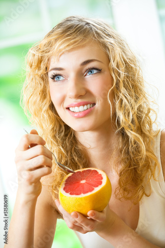 Cheerful blond woman eating grapefruit