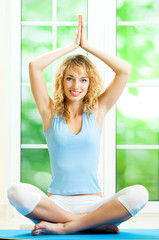 Blond woman meditating, indoors