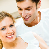 Cheerful smiling young couple, indoors