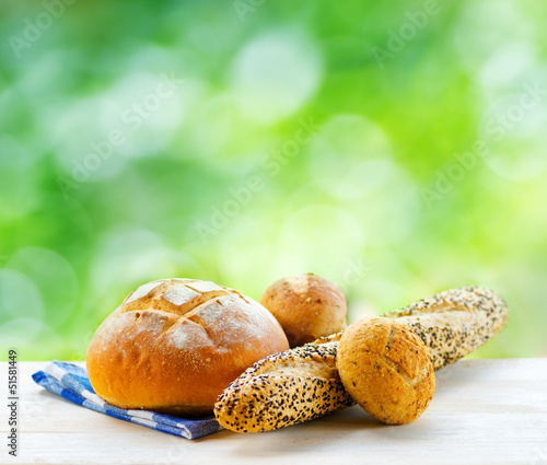 Fresh bread and checkered napkin on wooden table on rural backgr