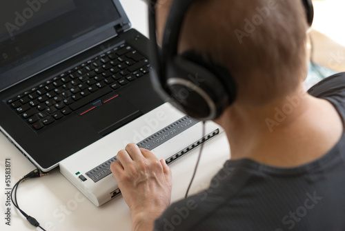Blind person working on computer with braille display and screen