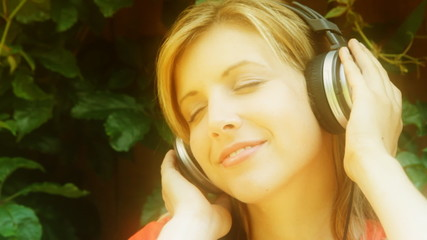 Young woman listens to music. Dreamy look.