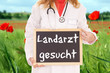 Ärztin mit Schild - Landarzt gesucht