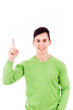 Happy young casual man pointing upwards over white background