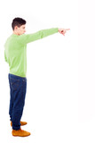 Young man pointing towards copyspace, isolated on a white backgr