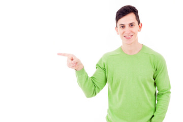 Happy smiling young man pointing towards copyspace, isolated on