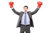 Young man in a suit and boxing gloves, celebrating a win