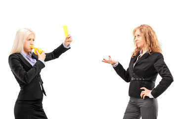 Woman in suit showing a yellow card and blowing a whistle to a f