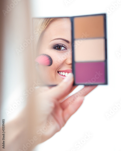 Woman applying cosmetics to her face