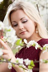 Beautiful blonde woman in blooming spring garden