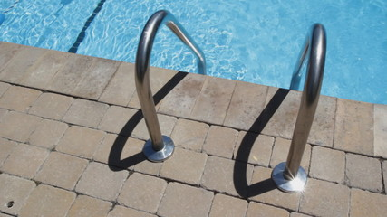 Swimming pool ladder beside clean, summer pool.