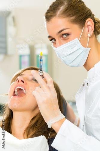 Zahnarzt hält eine Spritze - Narkose bei einer Patientin