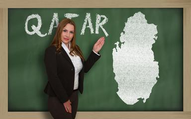 Teacher showing map of qatar on blackboard