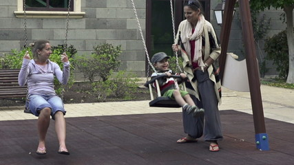 Girlfriends with kid playing on the swing, super slow motion