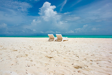 beach chairs on white sand by the ocean