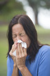 Woman sneezing tissue with flu or hayfever