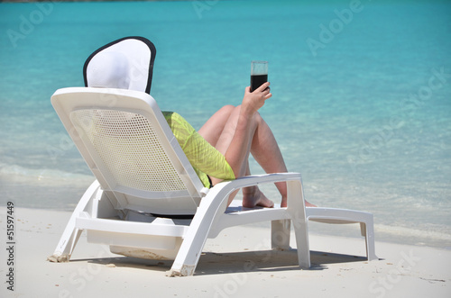 Girl with a glass of soda on the tropical beach