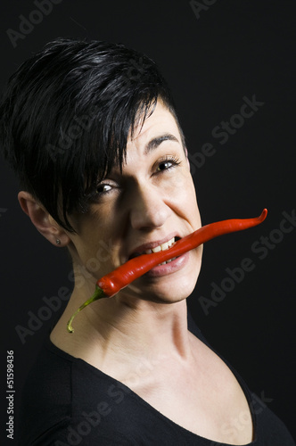 red chilli in the mouth of woman