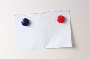 hoja de cuaderno colgada en nevera con iman