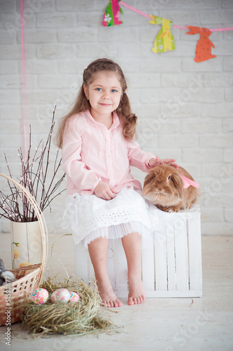 Little girl with rabbit and easter decorations