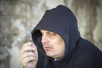 Drug addict men looks at the syringe in the hands