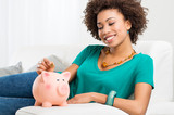 Woman Putting Coin In Piggybank