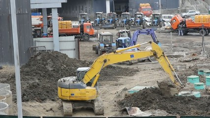 yellow track-type excavator digs the ground