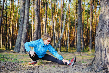 Fit young woman stretching in the forest