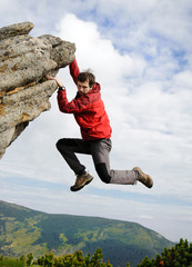 Young male climbing on a cliff