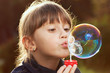 Little girl inflates a big bubble