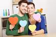 Junges schwules Paar mit vielen bunten Herzen