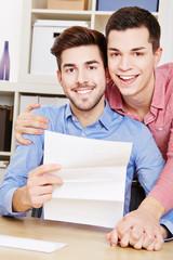 Schwules lachendes Paar mit Brief