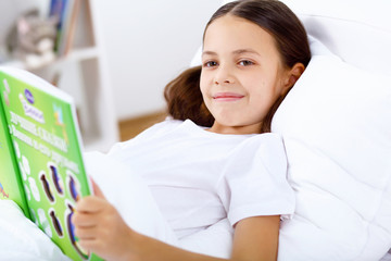 Girl with a book in bed at home