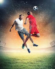 two football players striking ball