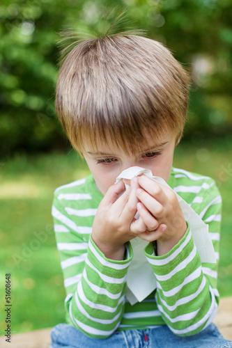 kleiner junge putzt sich die nase