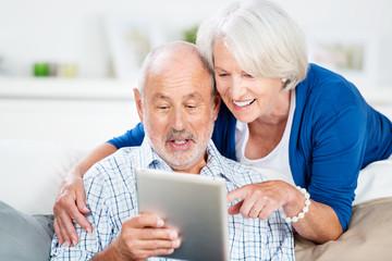 lachendes senioren-paar mit tablet