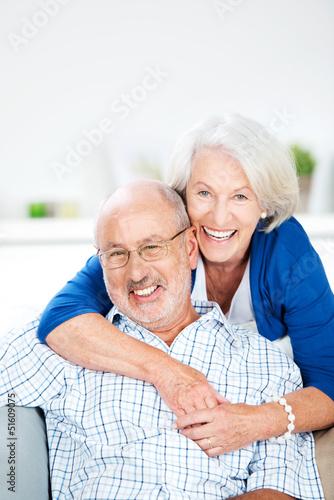 glückliches älteres paar umarmt sich auf dem sofa - 51609075