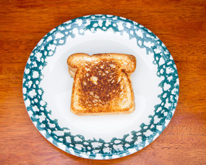 Piece of toast on a decorative plate