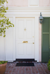 White front door of an upscale home with wreath