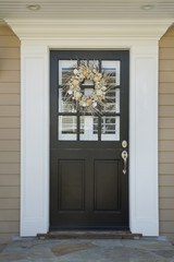Black front door of an upscale home with wreath