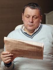 Portrait of senior man reading newspaper at home.