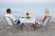 A young couple share a romantic dinner with candles and wine on