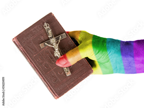 Old hand (woman) holding a very old bible, rainbow flag