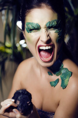 woman with creative make up like snake with rat in her hands
