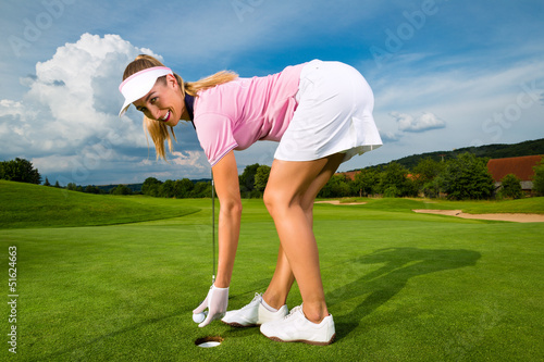 Young female golf player on course
