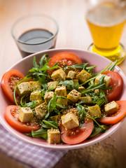 salad with tofu tomatoes arugula and sesame seeds, selective foc