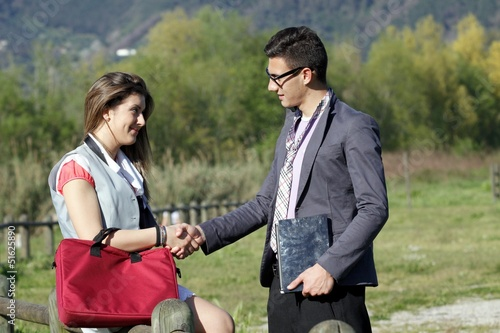 boy and girl business shake hands
