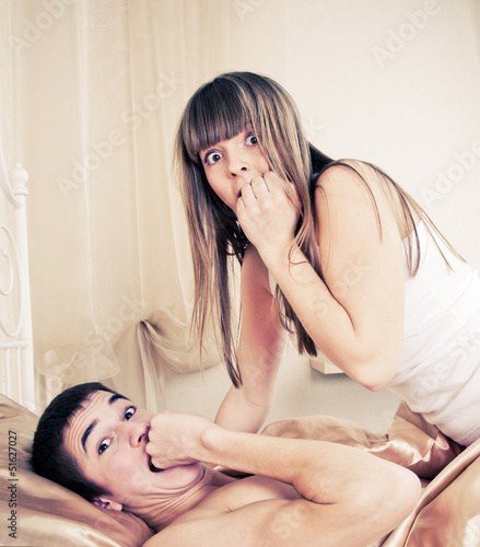 Surprised sex couple lying in bed